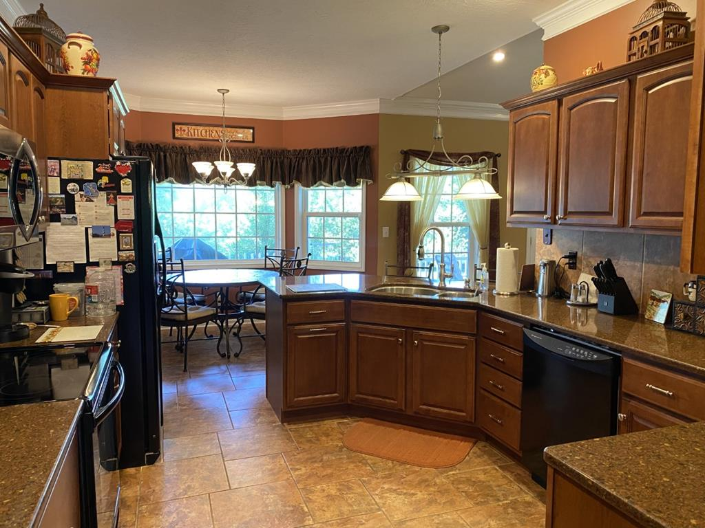 Kitchen has cherry stained cabinets and breakfast